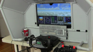 at the controls of this desktop home flight sim
